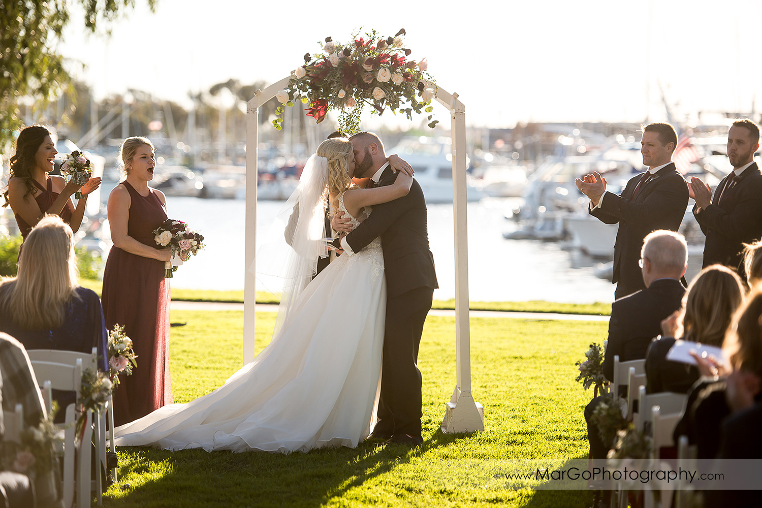 bride and groom kissing during wedding ceremony at San Diego Marina Village
