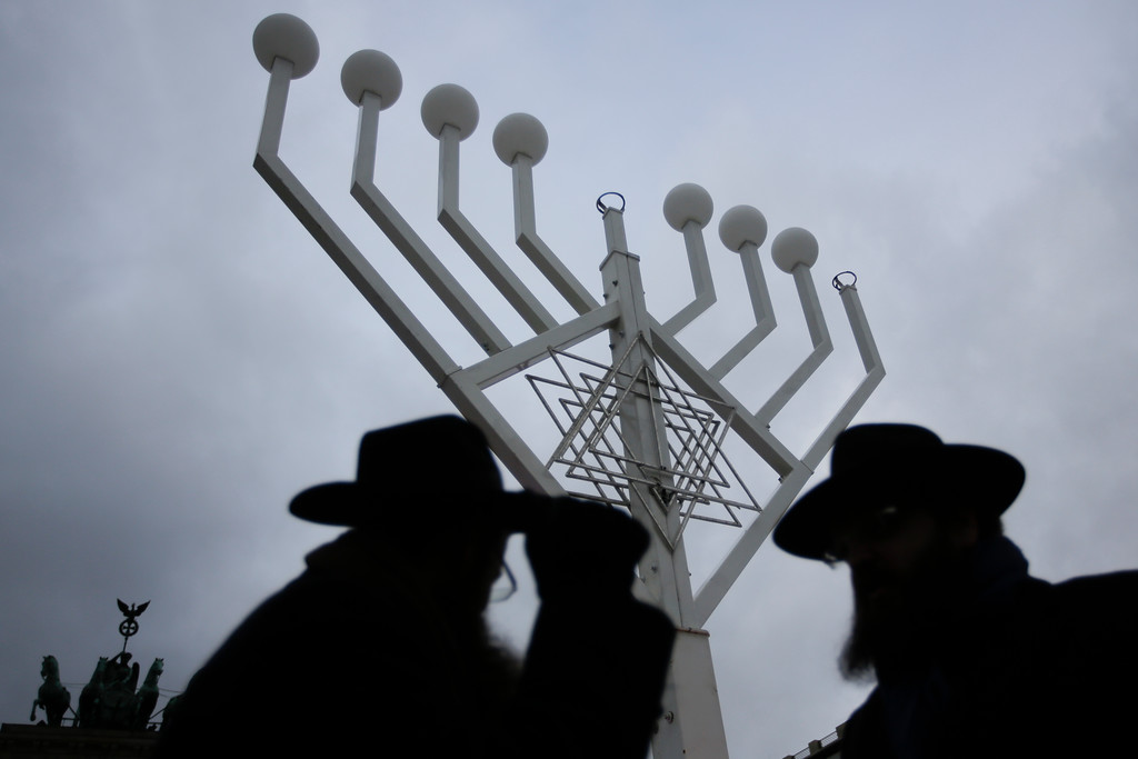 . Rabbi Yehuda Teichtal, right, and Rabbi Segal Shmoel, left, inspect a giant Hanukkah Menorah, set up by the Jewish Chabad Educational Center, at the Pariser Platz in Berlin, Tuesday, Dec. 12, 2017. (AP Photo/Markus Schreiber)