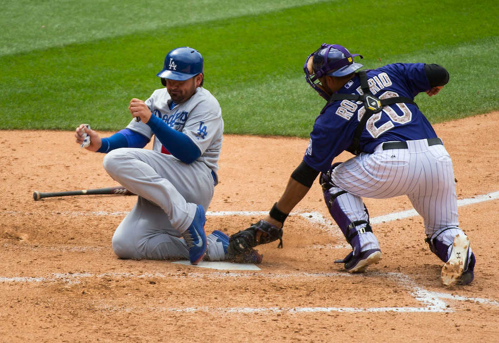 . Los Angeles Dodgers first baseman Adrian Gonzalez (23) slides at home plate as Colorado Rockies catcher Wilin Rosario (20) misses the tag on a throw from Colorado Rockies third baseman Nolan Arenado (28)  July 6, 2014 at Coors Field. Los Angeles Dodgers third baseman Juan Uribe (5) reached first base on a fielders choice. (Photo by John Leyba/The Denver Post)