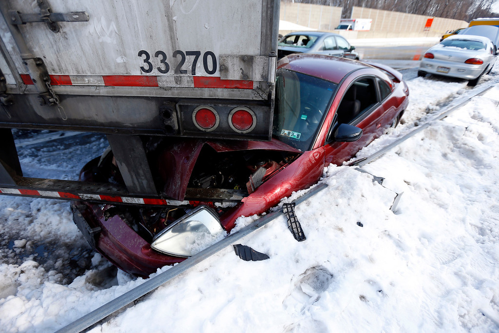 . Vehicles are piled up in an accident, Friday, Feb. 14, 2014, in Bensalem, Pa. Traffic accidents involving multiple tractor trailers and dozens of cars have completely blocked one side of the Pennsylvania Turnpike outside Philadelphia and caused some injuries. (AP Photo/Matt Rourke)