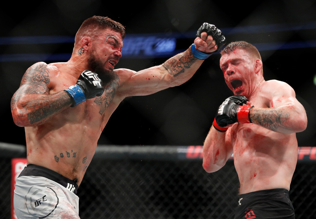 . Mike Perry, left, swings at Paul Felder during a welterweight mixed martial arts bout at UFC 226, Saturday, July 7, 2018, in Las Vegas. (AP Photo/John Locher)