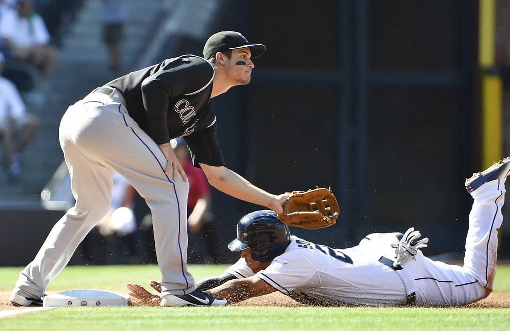 . SAN DIEGO, CA - AUGUST 13:  Yangervis Solarte #27 of the San Diego Padres slides safely into third base ahead of the throw to Nolan Arenado #28 of the Colorado Rockies during the first inning of a baseball game at Petco Park on August 13, 2014 in San Diego, California.  (Photo by Denis Poroy/Getty Images)