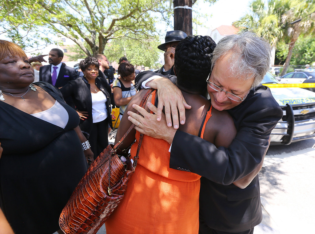 . John Tecklenburg hugs J. Denise Cromwell outside the Morris Brown AME Church after police cleared the church for safety reasons during a prayer vigil for the victims of Wednesday\'s shooting at Emanuel AME Church in Charleston, S.C., on Thursday, June 18, 2015.  Dylann Storm Roof, 21, was arrested Thursday in the slayings of several people, including the pastor, at a prayer meeting inside the historic black church. (Curtis Compton /Atlanta Journal-Constitution via AP)
