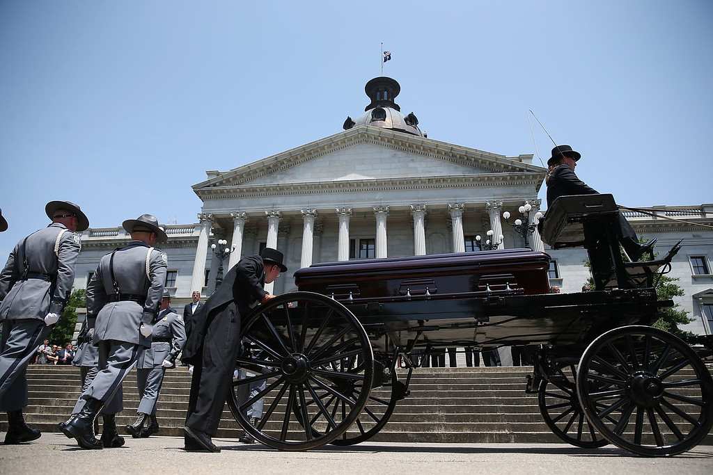 . South Carolina Highway Patrol Honor Guard prepare to carry the coffin of church pastor and South Carolina State Sen. Clementa Pinckney to lie in repose at the Statehouse Rotunda on June 24, 2015 in Columbia, South Carolina. Pinckney was one of nine people killed during a Bible study inside Emanuel AME church in Charleston. U.S. President Barack Obama and Vice President Joe Biden are expected to attend the funeral which is set for Friday June 26 at the TD Arena.  (Photo by Joe Raedle/Getty Images)