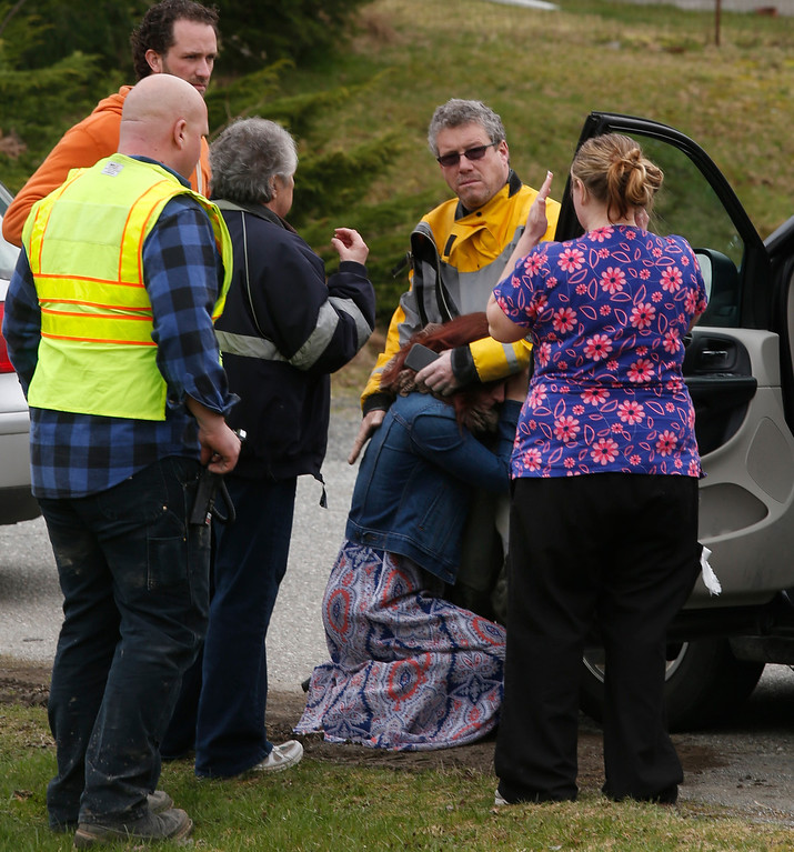 . A woman collapses near the Oso Fire Department as neighbors look for news regarding the fatal mudslide that washed over homes and over Highway 530 east of Oso, Wash., Saturday, March 22, 2014. Highway 530 was closed in both directions, and authorities confirmed at least 2 fatalities by Saturday afternoon. (AP Photo /The Daily Herald, Annie Mulligan)