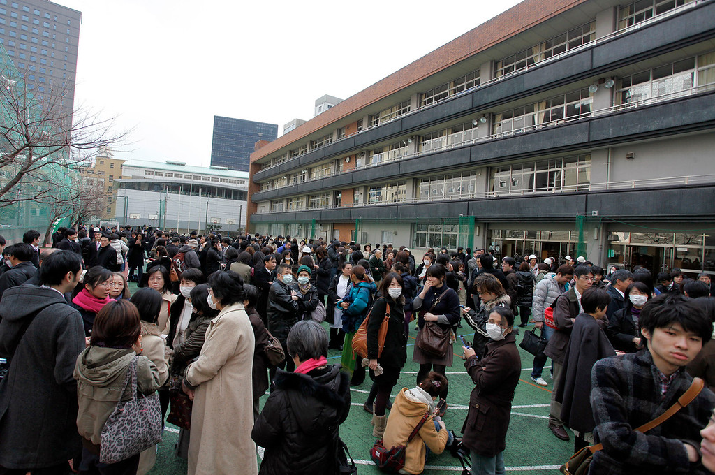 . People who have escaped from buildings wait in the grounds of a junior high school following an earthquake in Tokyo, Japan, on Friday, March 11, 2011. Japan was struck by its strongest earthquake on record, an 8.9-magnitude temblor that shook buildings across Tokyo and unleashed a seven-meter-high tsunami that killed hundreds as it engulfed towns on the northern coast. Photographer: Koichi Kamoshida/Bloomberg