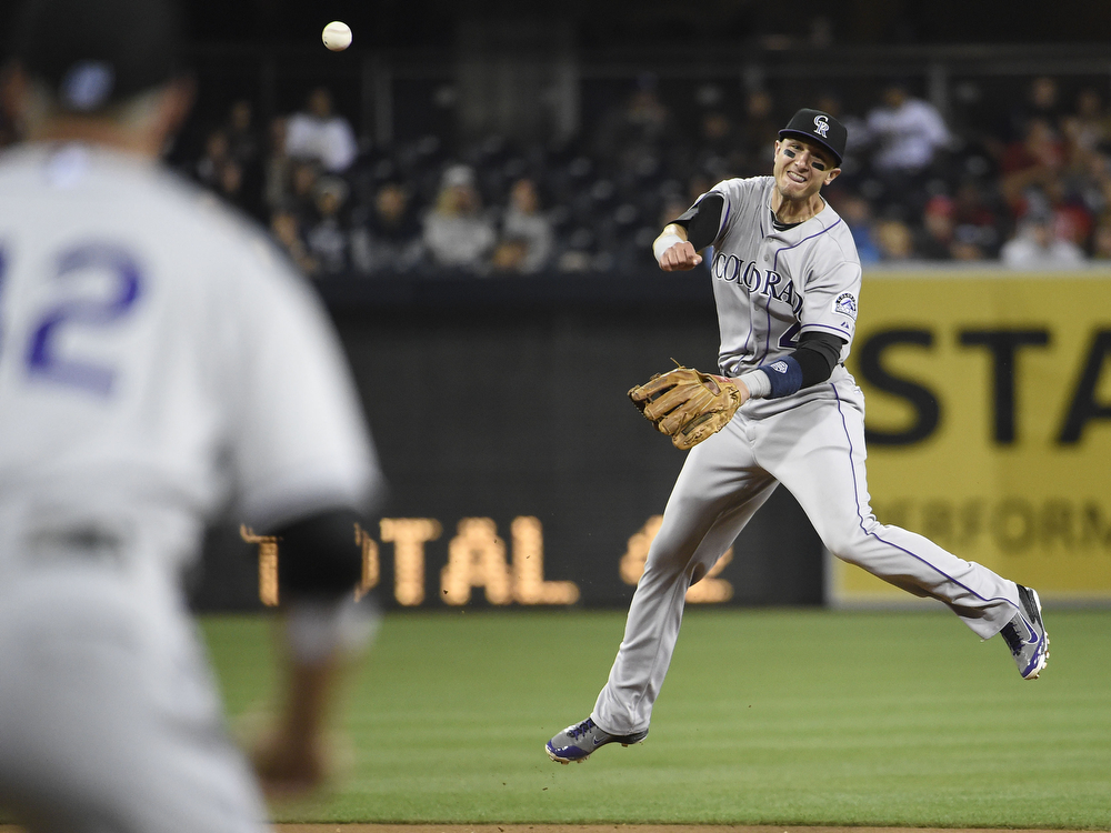 . SAN DIEGO, CA - APRIL 15:  Troy Tulowitzki of the Colorado Rockies throws to first base to get the out on Nick Hundley of the San Diego Padres during the second inning of a  baseball game at Petco Park April 15, 2014 in San Diego, California. All uniformed team members are wearing jersey number 42 in honor of Jackie Robinson Day. (Photo by Denis Poroy/Getty Images)