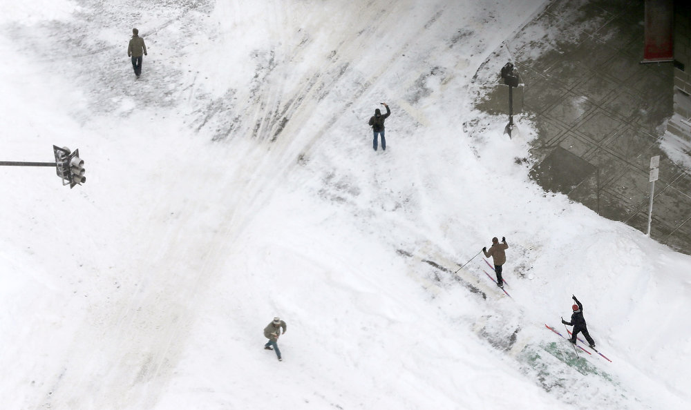 . People ski as other stand on a street in the Back Bay neighborhood following a powerful blizzard on February 9, 2013 in Boston, Massachusetts. The storm knocked out power to 650,000 and dumped more than two feet of snow in parts of New England.  (Photo by Mario Tama/Getty Images)
