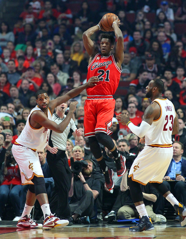 . Chicago Bulls guard Jimmy Butler (21) looks to pass between Cleveland Cavaliers center Tristan Thompson (13) and forward LeBron James (23) during the first half of an NBA basketball game in Chicago, on Saturday, April 9, 2016.  (AP Photo/Jeff Haynes)