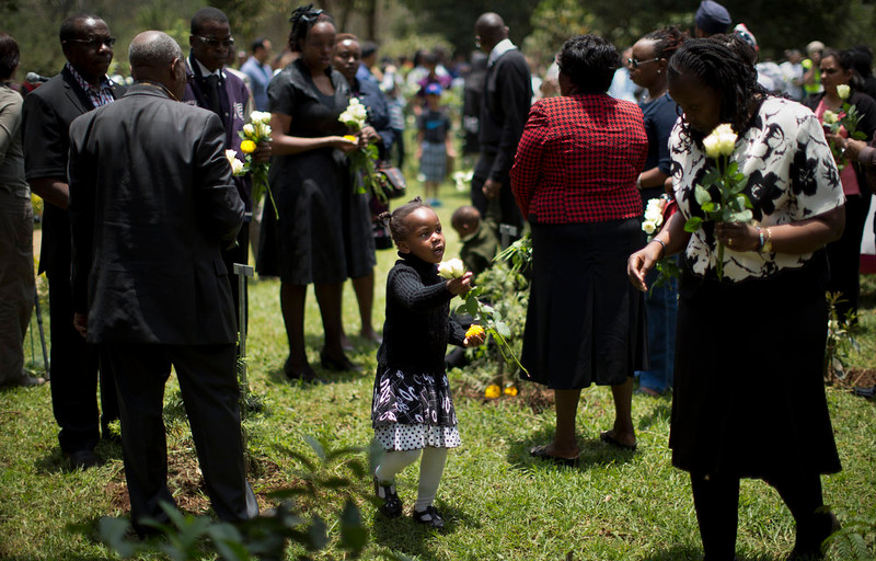 . A young girl hands a white rose to an elder relative, right, as they prepare to lay flowers and remember the victims of the Westgate Mall attack, at the Amani Garden memorial site in the Karura Forest in Nairobi, Kenya Sunday, Sept. 21, 2014. Kenya is marking one year since four gunmen stormed the upscale Westgate Mall in Nairobi, killing 67 people, and a memorial plaque with the names of the victims was unveiled at the popular forest on the edge of the city. (AP Photo/Ben Curtis)