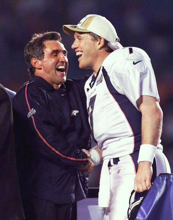 . Denver Broncos quarterback John Elway, right, and head coach Mike Shanahan laugh on the victory stand following their 34-19 win over the Atlanta Falcons in Super Bowl XXXIII in Miami.  (AP Photo/Amy Sancetta, File)
