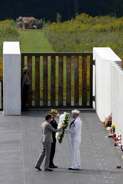 . Secretary of the Interior Sally Jewell, left, and Gordon Felt, center, brother of Edward P. Felt, a passenger on Flight 93, place a wreath with the help of Navy honor guard Matthew Konchan, of Johnstown, Pa., in front of  the wall containing the names of the 40 crew and passengers on Flight 93 at the Flight 93 National Memorial on Wednesday, Sept. 11, 2013 in Shanksville. The boulder, top, marks the area of the plane\'s impact. (AP Photo/Gene J. Puskar)