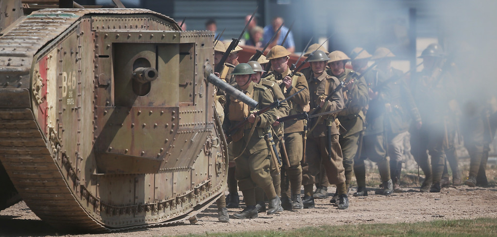 . BOVINGTON, UNITED KINGDOM - AUGUST 04:  Members of a living history society walk behind a replica tank during a World War One centenary ceremony at the Tank Museum, Bovington on August 4, 2014 in England. Monday August 4, 2014  marks the 100th anniversary of Great Britain\'s declaration of war on Germany. In 1914 British Prime Minister Herbert Asquith announced at 11 pm that Britain was to enter the war after Germany had violated Belgium neutrality. The First World War or the Great War lasted until 11 November 1918 and is recognised as one of the deadliest historical conflicts with millions of causalities. A series of events commemorating the 100th anniversary are taking place throughout the day.  (Photo by Peter Macdiarmid/Getty Images)