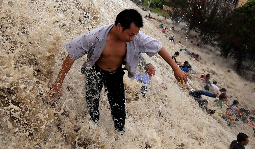 """. This picture taken on August 22, 2013 shows onlookers being washed away from huge waves from the \""""Haining tide\"""" - a daily occurrence when the river tides hit the banks of the city - as the waves surged higher than usual due to the influence of Typhoon Trami in the region in Haining, in eastern China\'s Zhejiang province.     AFP PHOTOSTR/AFP/Getty Images"""