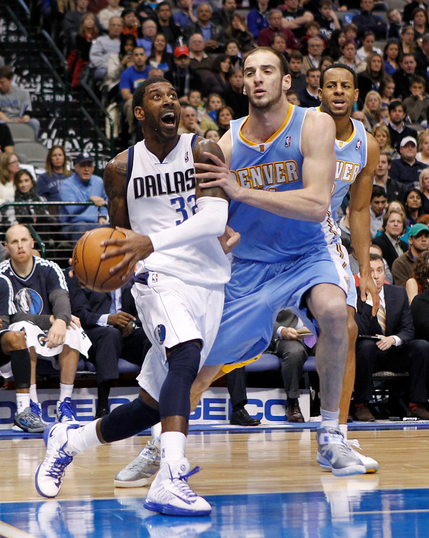 . Dallas Mavericks guard O.J. Mayo drives on Denver Nuggets center Kosta Koufos during the first half of their NBA basketball game in Dallas, Texas, December 28, 2012.  REUTERS/Mike Stone