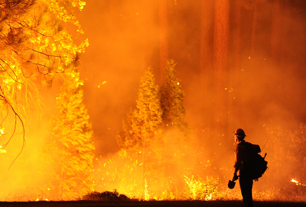 . Big Bear firefighter Jon Curtis keeps a close eye on a \'slop over\' fire that jumped Hwy 120 just east of Hardin Flat Road while fighting the Rim Fire, which continues to burn uncontrolled in the Stanislaus National Forest Saturday Aug. 24, 2013. (AP Photo/The Modesto Bee, Elias Funez)