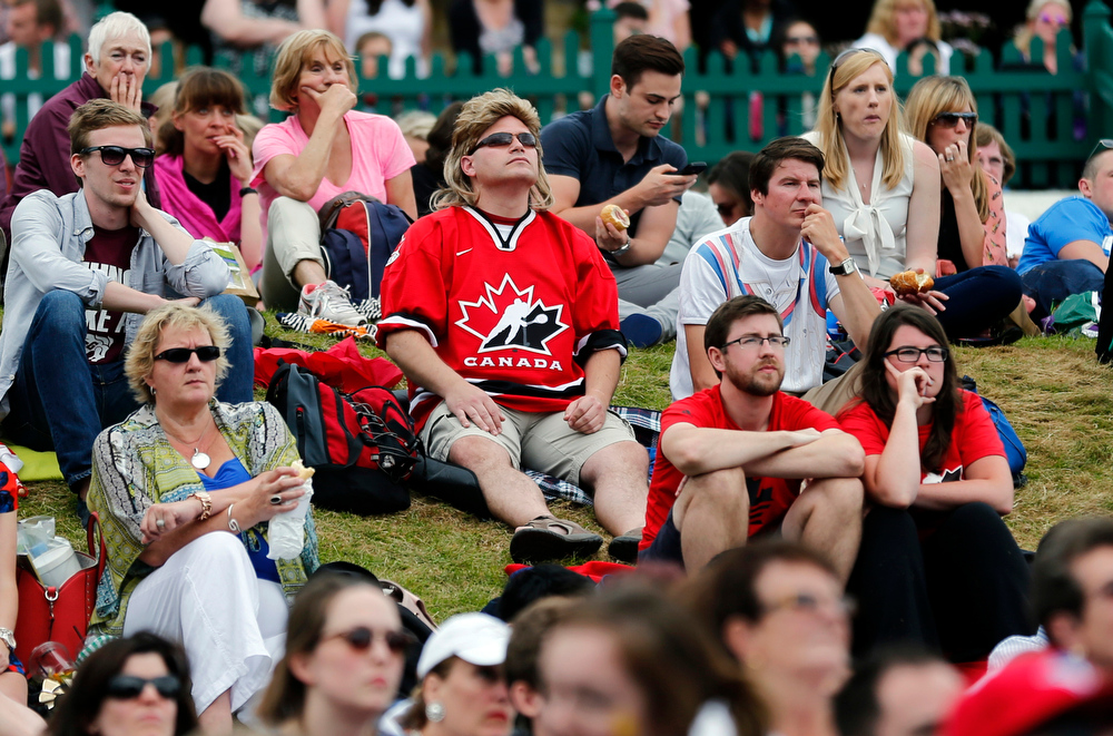 Description of . Canadian Darcy Dayment, center, originally from London, Ontario but who now lives in London, England, watches the women's singles final between Eugenie Bouchard of Canada and Petra Kvitova of Czech Republic on a large video screen with other spectators at the All England Lawn Tennis Championships in Wimbledon, London Saturday, July 5, 2014. (AP Photo/Ben Curtis)