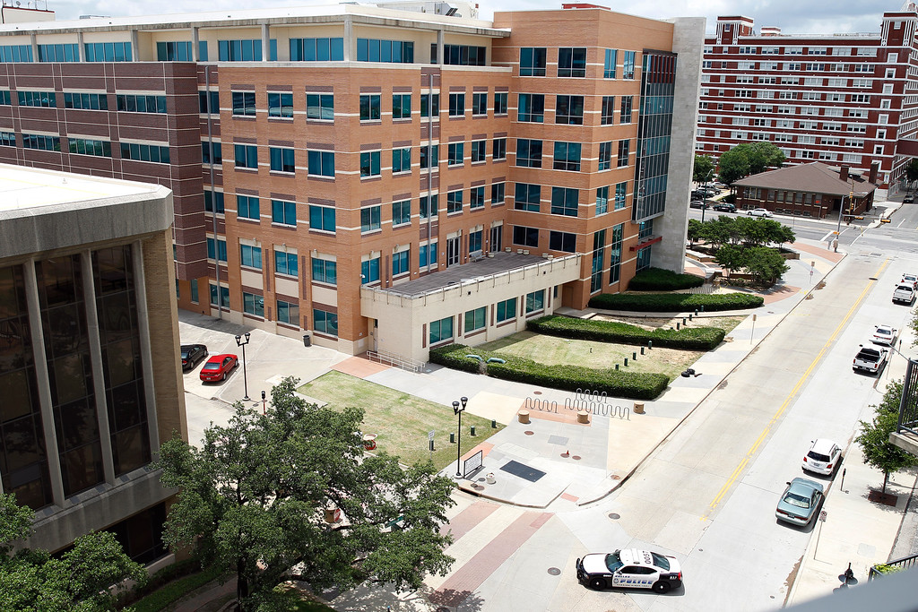 . Dallas police headquarters, center, is shown as a police vehicle below blocks off  Belleview Street where a crime scene investigation continues after an early morning attack on the police took place Saturday June 13, 2015, in Dallas. A man suspected of spraying Dallas Police Headquarters with gunfire early on Saturday has been found dead in a van after a police sniper shot him and pipe bombs found in the vehicle were exploded, a police spokesman said. (AP Photo/Tony Gutierrez)