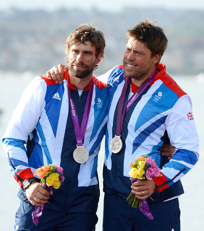 """. File -This August 5, 2012 file photo shows Britain\'s Andrew Simpson (R) and Iain Percy celebrating on the podium after winning the silver medal in the Star sailing class at the London 2012 Olympic Games in Weymouth, England. A sailor killed when a Swedish catamaran capzied May 9, 2013 while training for the upcoming America\'s Cup races was identified as Olympic medal-winning Briton Andrew \""""Bart\"""" Simpson.  \""""It is with immense sadness that Artemis Racing confirms the tragic death of crewmember,\"""" said a statement on the America\'s Cup website, after the accident during training in San Francisco Bay.  \""""Simpson ... was one of the 11-man crew aboard Artemis Racing\'s AC72 catamaran which capsized during training on San Francisco Bay ahead of this summer\'s America\'s Cup.  It said he was \""""trapped underneath the boat and despite attempts to revive him, by doctors afloat and subsequently ashore, his life was lost,\"""" adding that all other crewmembers were accounted for.   \""""The entire Artemis Racing team is devastated by what happened,\"""" said Artemis Racing chief executive Paul Cayard. \""""Our heartfelt condolences are with Andrew\'s wife and family.\""""   AFP PHOTO / Files / William WESTWILLIAM WEST/AFP/Getty Images"""