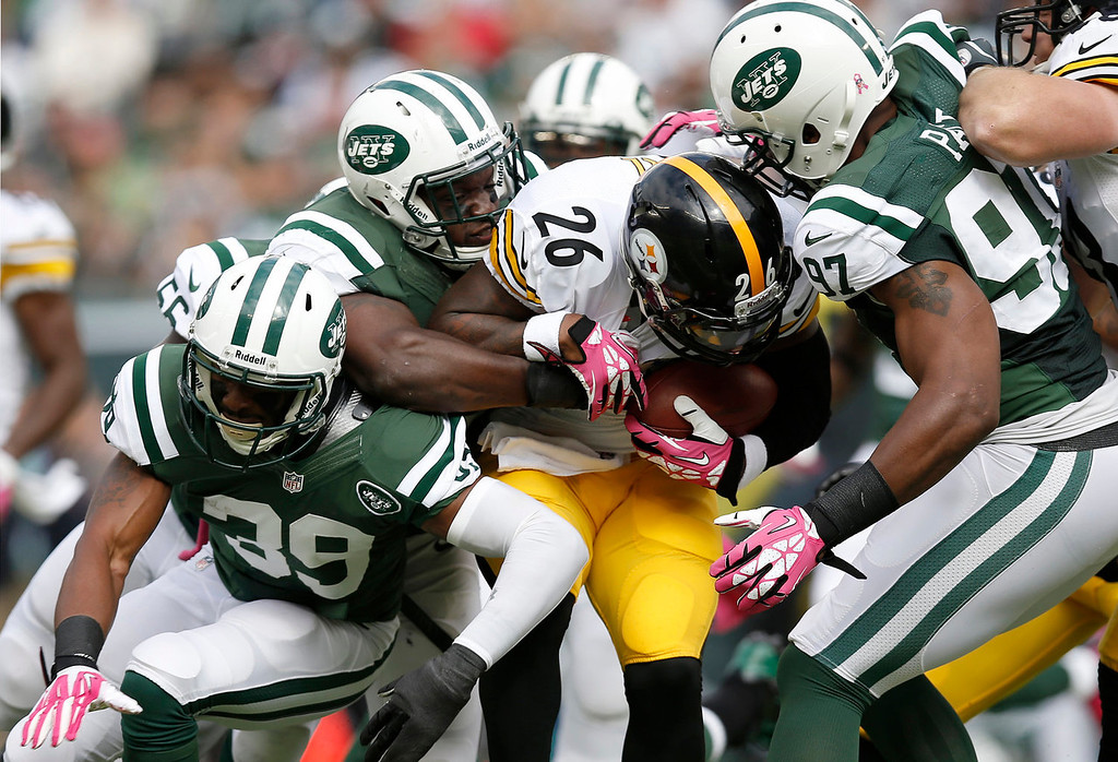 . Pittsburgh Steelers running back Le\'Veon Bell (26) is tackled by New York Jets\' Calvin Pace (97), David Harris, and Antonio Allen (39) during the first half of an NFL football game Sunday, Oct. 13, 2013, in East Rutherford, N.J.  (AP Photo/Kathy Willens)