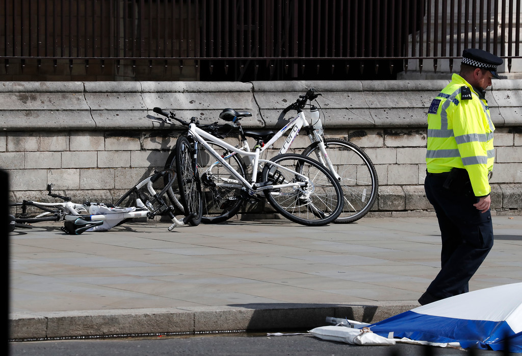 . Bicycles are placed against a wall near the scene where a car crashed into security barriers outside the Houses of Parliament in London, Tuesday, Aug. 14, 2018. Authorities said in a statement Tuesday that a man in his 20s was arrested on suspicion of terrorist offenses after a silver Ford Fiesta collided with a number of cyclists and pedestrians before crashing into the barriers during the morning rush hour. (AP Photo/Frank Augstein)