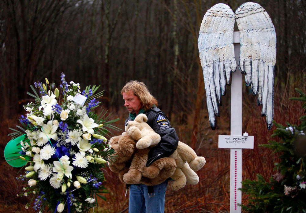 Description of . Patrick Carroll holds stuffed animals as he looks at a memorial for the victims of Sandy Hook Elementary School shooting in Newtown, Connecticut December 18, 2012. U.S. authorities continue to investigate the December 14 massacre in Connecticut in which a heavily armed gunman entered Sandy Hook Elementary school and shot and killed 20 children and six adults. The incident, resulting in 28 deaths, including the gunman and his mother, has prompted a fresh debate on U.S. gun control. REUTERS/Joshua Lott