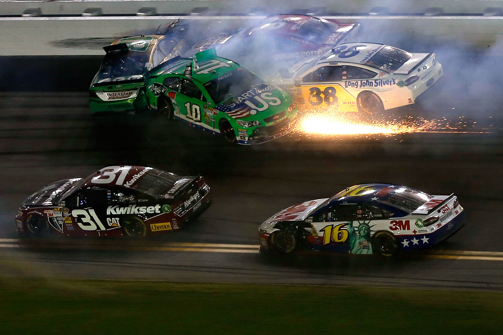 . DAYTONA BEACH, FL - JULY 06:  Kyle Busch, driver of the #18 Interstate Batteries Toyota, Danica Patrick, driver of the #10 GoDaddy.com Chevrolet, JJ Yeley, driver of the #36 Golden Corral Chevrolet and David Gilliland, driver of the #38 Long John Silver\'s Ford are involved in a wreck late in the race during the NASCAR Sprint Cup Series Coke Zero 400 at Daytona International Speedway on July 6, 2013 in Daytona Beach, Florida.  (Photo by Scott Halleran/Getty Images)