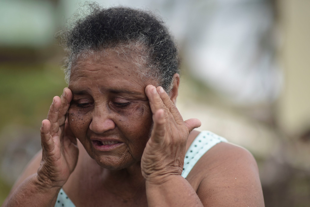 . El Negro community resident Irma Torres Rodriguez tries to stay calm after loosing a portion of her roof to the fury of Hurricane Maria, in Puerto Rico, Thursday, September 21, 2017. As of Thursday evening, Maria was moving off the northern coast of the Dominican Republic with winds of 120 mph (195 kph). The storm was expected to approach the Turks and Caicos Islands and the Bahamas late Thursday and early Friday. (AP Photo/Carlos Giusti)