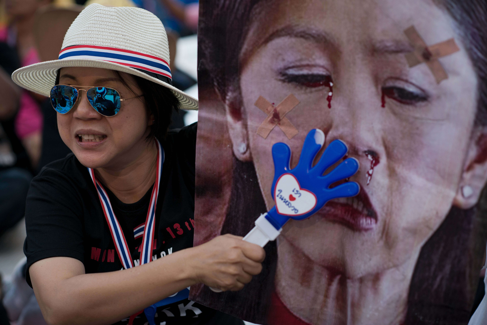 . A Thai anti-government protester slaps a mocked-up picture of Thai Prime Minister Yingluck Shinawatra with a clapper outside the MBK shopping complex in Bangkok on January 16, 2014. Thailand\'s government pleaded with police to arrest opposition protest leaders who have threatened to take the prime minister captive and paralyzed parts of central Bangkok. (NICOLAS ASFOURI/AFP/Getty Images)