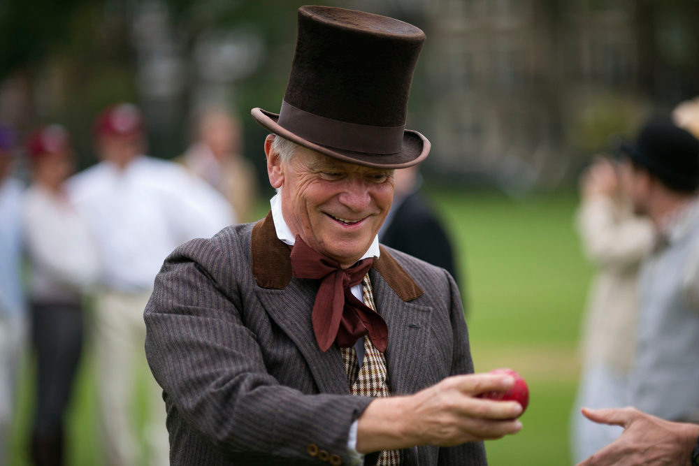 . British author and former politician Jeffrey Archer hands over a cricket ball before umpiring a Victorian-era costume themed cricket match on a wicket in Vincent Square, central London, Wednesday, May 29, 2013.  The two-over-a-side Victorian match was held Wednesday to mark the launch of the 150th anniversary edition of the Wisden Cricketers\' Almanac.  (AP Photo/Matt Dunham)