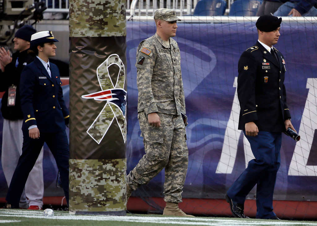 . Members of the U.S. military walk past a goal post decorated to acknowledge Salute to Service activities before an NFL football game between the New England Patriots and the Detroit Lions Sunday, Nov. 23, 2014, in Foxborough, Mass. (AP Photo/Stephan Savoia)