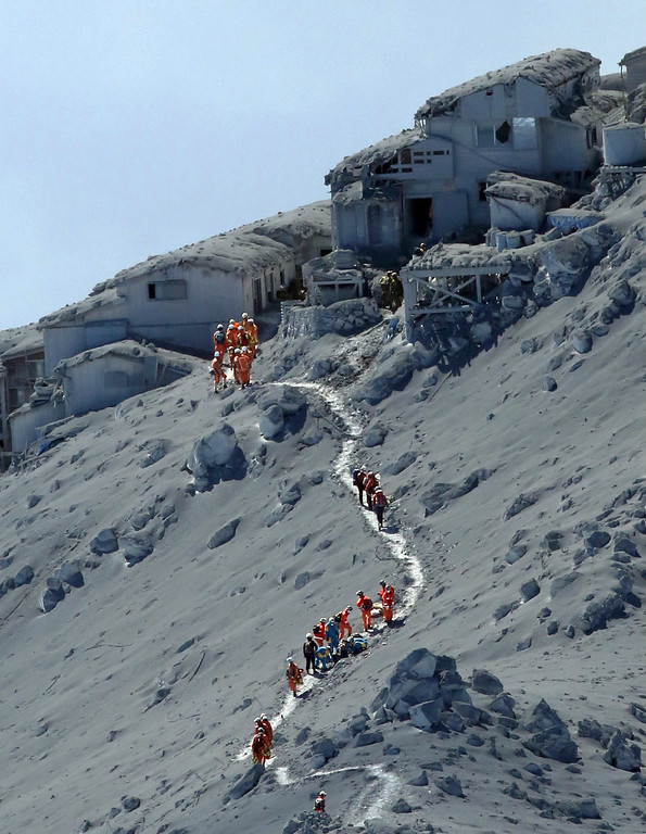 . This aerial picture taken on September 28, 2014 shows rescue workers and Self Defence Force soldiers searching for missing climbers and survivors among ash covered mountain cottages on the top of Mount Ontake at Nagano prefecture, one day after Japan\'s volcano Ontake erupted in central Japan, which straddling Nagano and Gifu prefecture. Rescuers rushed to help dozens of hikers stranded on an erupting volcano in central Japan with six people believed to be buried under ash and dozens injured.        (JIJI PRESS/AFP/Getty Images)