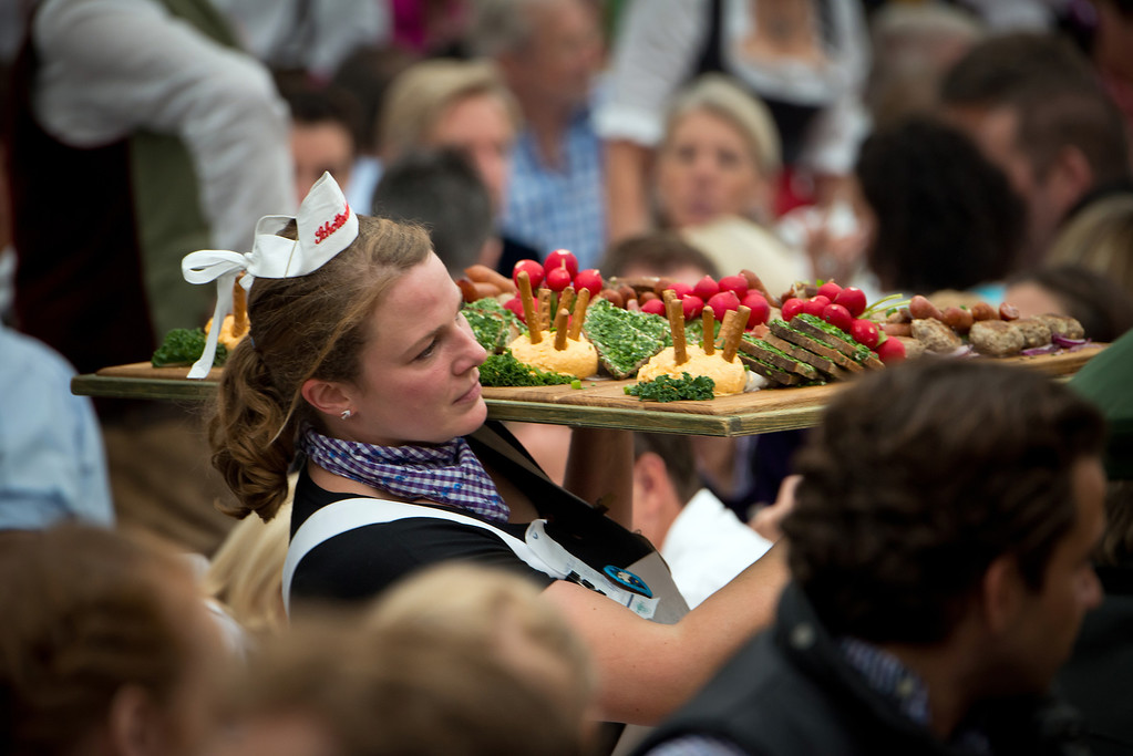 ". A waitress carries Bavarian food at the Oktoberfest 2013 beer festival at the Schottenhamel-tent at Theresienwiese on September 21, 2013 in Munich, Germany. Shortly before, Munich mayor Christian Ude (SPD) had tapped the first barrel with the traditional ""O\'zapft is!\"" (\""It\'s tapped!\"") to launch the festival. The Munich Oktoberfest, which this year will run from September 21 through October 6, is the world\'s largest beer fest and draws millions of visitors. (Photo by Joerg Koch/Getty Images)"