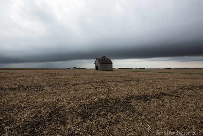 An abandonded house in the middle of a harvested field with a storm front in the distance.
