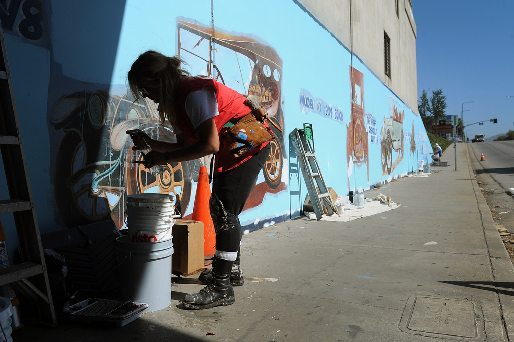 """. Kelly Forbes prepares to paint during restoration of the mural \""""Panorama: G.M. Recollections from the Past,\"""" on Van Nuys Boulevard in Panorama City, Thursday, June 20, 2013. The original mural was painted by Alfredo Diaz Flores in 1998 and pays homage to the General Motors plant that used to be near the mural site. (Michael Owen Baker/Staff Photographer)"""