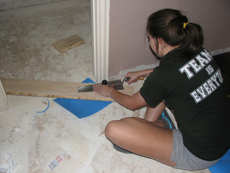Alli attempting to saw the molding and door jamb.