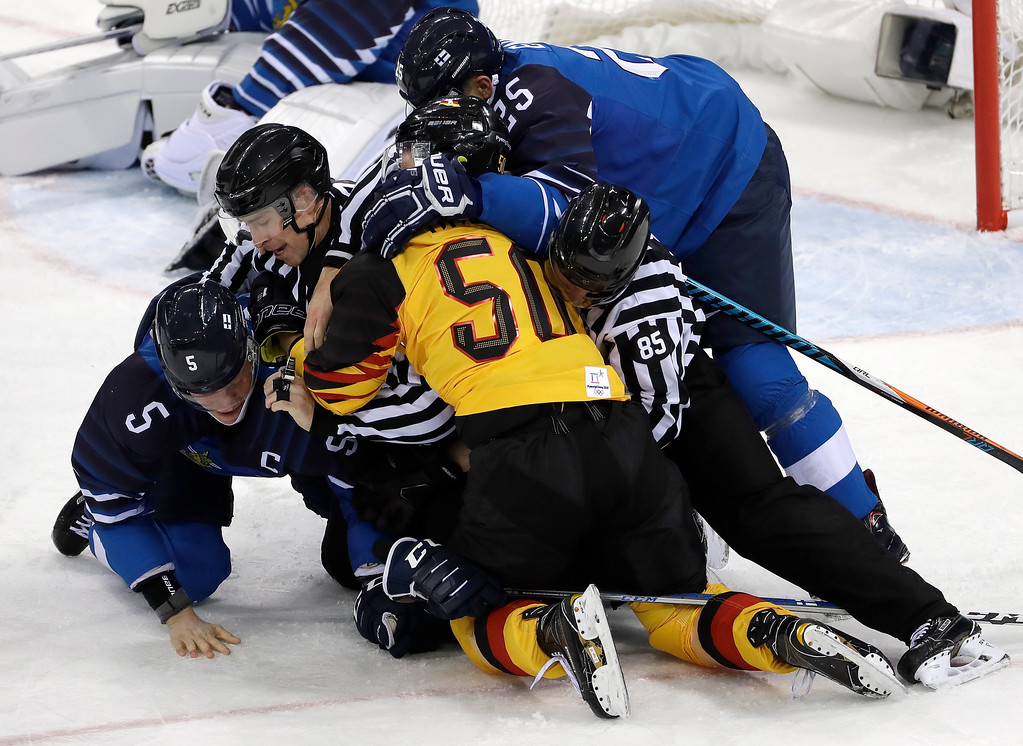 . Referees break up a fight between Lasse Kukkonen (5), of Finland, and Patrick Hager (50), of Germany, during the second period of the preliminary round of the men\'s hockey game at the 2018 Winter Olympics in Gangneung, South Korea, Thursday, Feb. 15, 2018. (AP Photo/Matt Slocum)