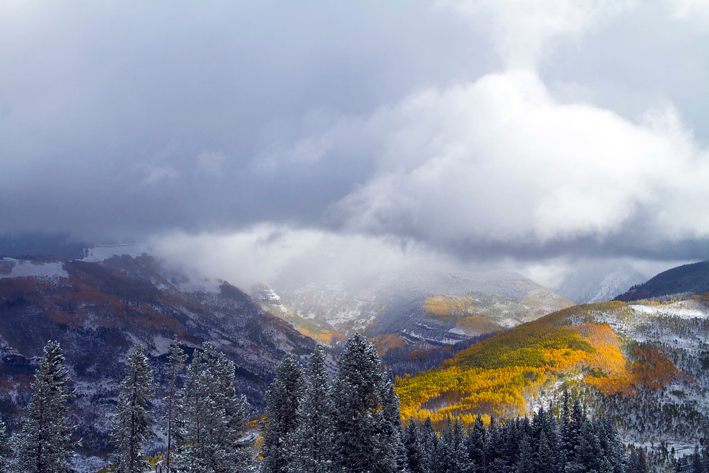 . This photo provided by Vail Resorts shows the sun highlighting colorful Aspen trees as it shines through the clouds during a snowstorm Friday, Oct. 4, 2013. As much as a foot of snow is forecast for some of the mountain areas in Colorado. (AP Photo/Vail Resorts, Andrew Taylor)