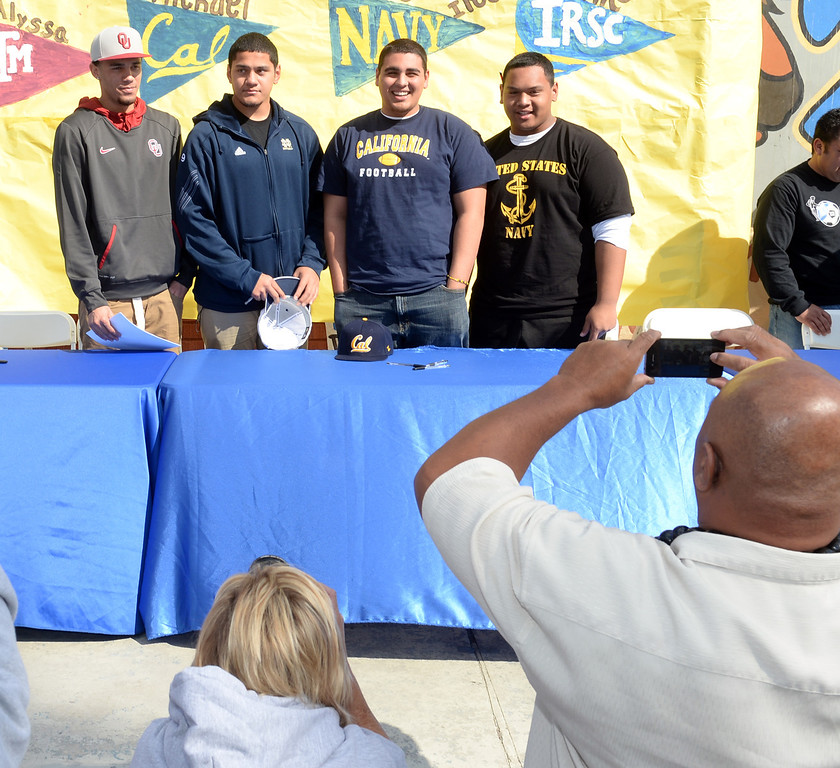 . Football players, from left, Dallis Todd, Oklahoma, Tyler Luatua, Notre Dame, Michael Trani, Cal, and Nofo Ti\'i, Navy, appear during National Signing Day at La Mirada High School on Wednesday February 5, 2014. (Staff Photo by Keith Durflinger/Whittier Daily News)