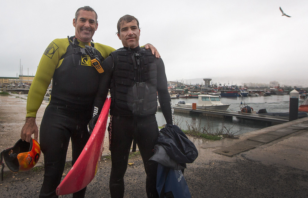 . Surfers Carlos Burle, right, from Brazil, and Garret McNamara, from the US, pose for a photo after Burle surfed a big wave at the Praia do Norte, north beach, at the fishing village of Nazare in Portugal\'s Atlantic coast Monday, Oct. 28 2013.  (AP Photo/Miguel Barreira)