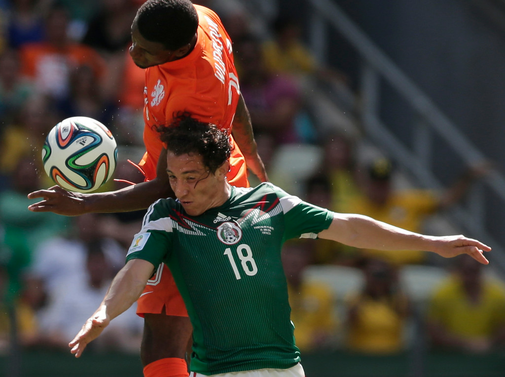 . Mexico\'s Andres Guardado (18) and Netherlands\' Georginio Wijnaldum go for a header during the World Cup round of 16 soccer match between the Netherlands and Mexico at the Arena Castelao in Fortaleza, Brazil, Sunday, June 29, 2014. (AP Photo/Marcio Jose Sanchez)