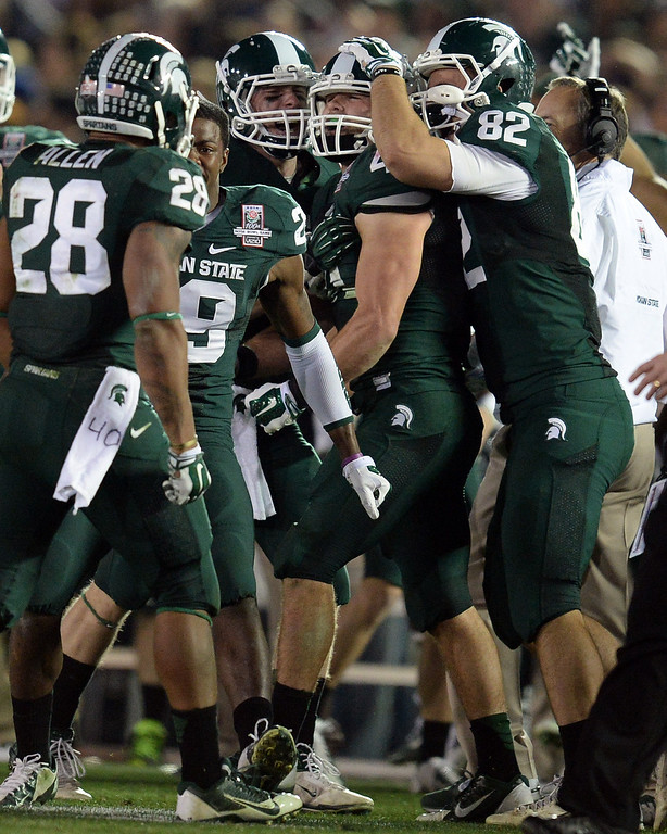 . Michigan State\'s Kyler Elsworth #41 is mobbed by teammates after stoping Stanford\'s Ryan Hewitt #85 on 4th and 1 late in the 4th quarter during the 100th Rose Bowl game in Pasadena Wednesday, January 1, 2014. Michigan State defeated Stanford 24-20. (Photo by Hans Gutknecht/Los Angeles Daily News)