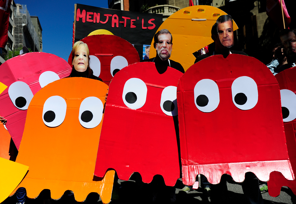 Description of . Demonstrators dressed up as characters of the video game Pac-Man and wearing masks of Spanish Prime Minister Mariano Rajoy (C) and German Chancellor Angela Merkel (L), take part a Labour Day march against the Spanish government's austerity policies in the centre of Barcelona on May 1, 2013. Tens of thousands protested across the globe for May Day to press for workers' rights amid tough economic times and to back an array of other causes.   JOSEP LAGO/AFP/Getty Images