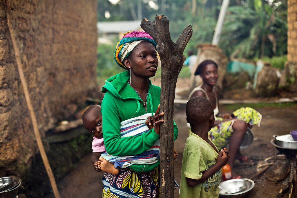 . In this photo taken Sunday Nov. 23, 2014, women gather  in the Guinean village of Meliandou, some 400 miles (600 kms) south-east of Conakry, Guinea, believed to be Ebola\'s ground zero.  (AP Photo/Jerome Delay)