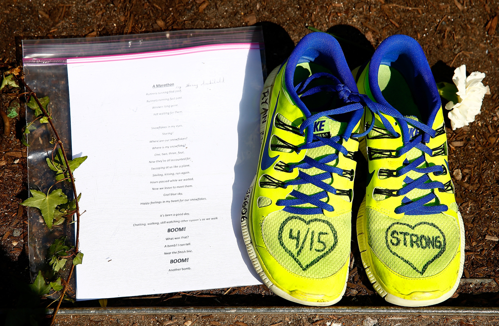 . A note and a pair of shoes are left at the site of the second bomb along Boylston Street near the finish line of the Boston Marathon prior to the start of the B.A.A. Tribute Run on April 19, 2014 in Boston, Massachusetts.  (Photo by Jared Wickerham/Getty Images)