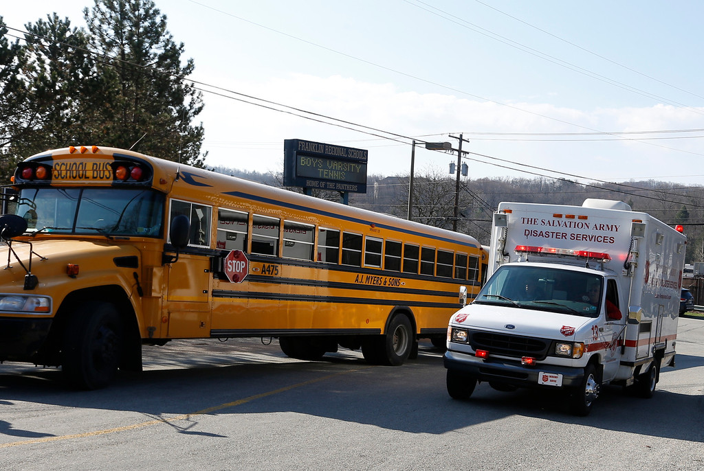 . A Salvation Army disaster services vehicle drives past a school bus onto the campus of the Franklin Regional School District where several people were stabbed at Franklin Regional High School, Wednesday, April 9, 2014 in Murrysville, Pa., near Pittsburgh. The suspect, a male student, was taken into custody and being questioned. (AP Photo/Keith Srakocic)