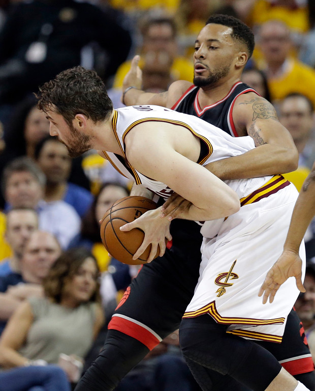 . Toronto Raptors\' Norman Powell, back, fouls Cleveland Cavaliers\' Kevin Love (0) in the first half in Game 1 of a second-round NBA basketball playoff series, Monday, May 1, 2017, in Cleveland. (AP Photo/Tony Dejak)