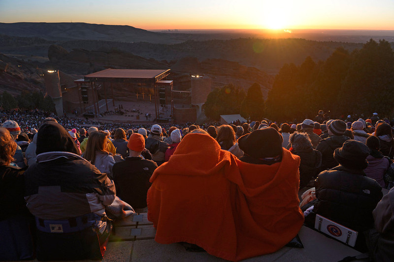 . People stay huddled underneath warm blankets as they watch the sun break the horizon as it rises in the east.  Thousands of people turned out for the sixty sixth annual Easter sunrise service at Red Rocks Amphitheatre in Golden on March 31st, 2013.The sun rose at 6:45 am under cloudless skies and this year\'s service was pleasant with warmer temperatures than in previous years.  The service, sponsored by the Colorado Council of Churches, was led by Reverend Dr. Jim Ryan and presided over by Reverend Dr. Janet Forbes.  (Photo By Helen H. Richardson/ The Denver Post)