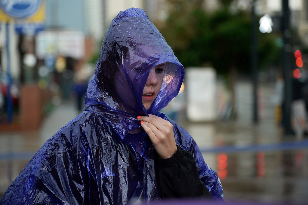 . Sarah Hogan, 20, of Wichita, Kansas, covers up as she leaves the stadium to take cover from the rain prior to the Colorado Rockies Los Angeles Dodgers game June 8, 2014 at Coors Field. (Photo by John Leyba/The Denver Post)