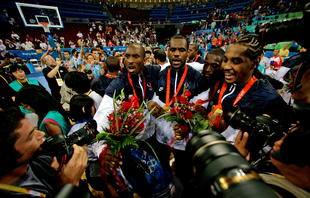 . USA\'s, from left, Kobe Bryant, LeBron James, Dwyane Wade and Carmelo Anthony surrounded by photographers as they celebrate after beating Spain 118-107 in the men\'s gold medal basketball game at the Beijing 2008 Olympics in Beijing, Sunday, Aug. 24, 2008.   (AP Photo/Dusan Vranic)